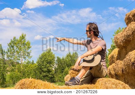 Handsome Man With Hat Sitting On Straw Bales And Pointing His Finger Toward The Blue Sky.
