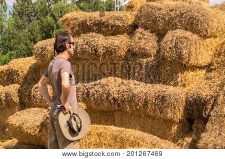 Handsome Man With Hat Standing With Hands On His Waist Near Straw Bales.