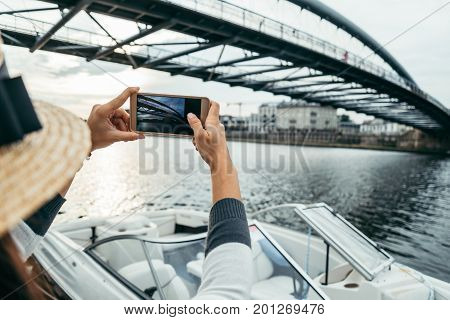 woman is taking picture while sitting on pier in the morning, boat and bridge on background