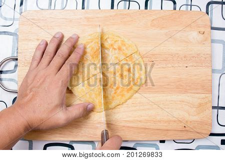 Chef cutting Roti on wooden broad / Cooking green curry concept
