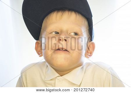Portrait Of A Little Boy In A Cap And A White Shirt.