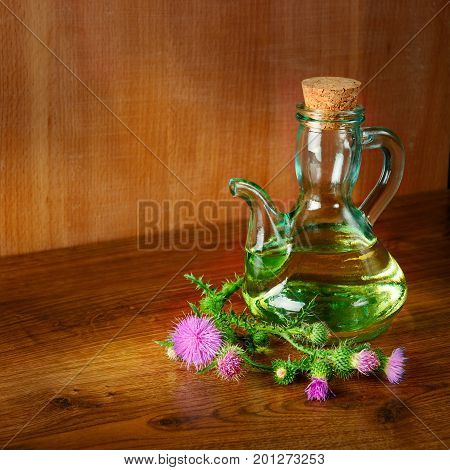 Oil and flowers of milk thistle on wooden background/