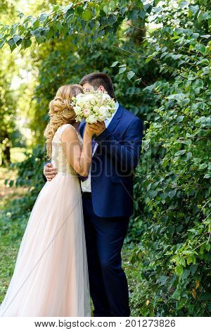 Happy Bride And Groom With Bridal Bouquet  Kissing In Park On Summer Wedding Day. Kissing Wedding Co