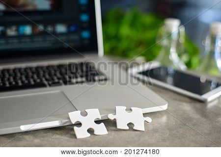 Two puzzles on laptop with blur background symbol of association and connection. business strategy. Selected focusing .