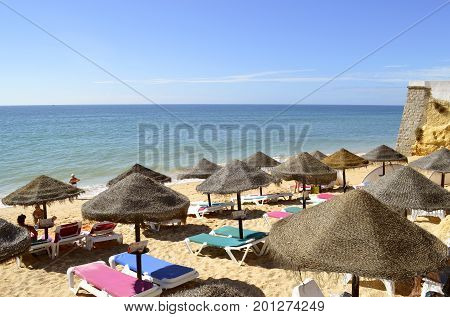 Armacao De Pera Beach Algarve Portugal - October 8 2014 : Tourists enjoying sunny weather on Armacao De Pera Beach on the Algarve coast