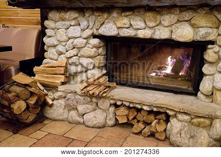 Stone fireplace with burning fire in country cottage. Flames of fire burning. Firewood against fireplace