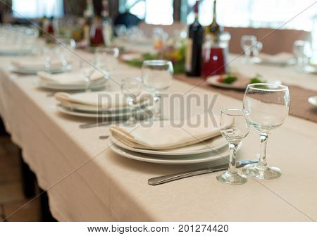 Empty glasses set in restaurant. Table setting selective focus. Table served for wedding banquet close up view. Beige serviette on white empty plate on dinner table