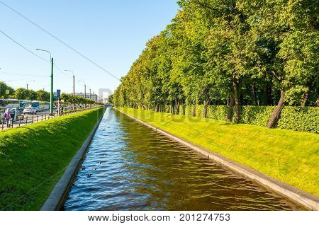 ST PETERSBURG RUSSIA - AUGUST 15 2017. Summer landscape of St Petersburg Russia - Swan Canal and summer park with green trees in sunny weather. St Petersburg Russia city landscape