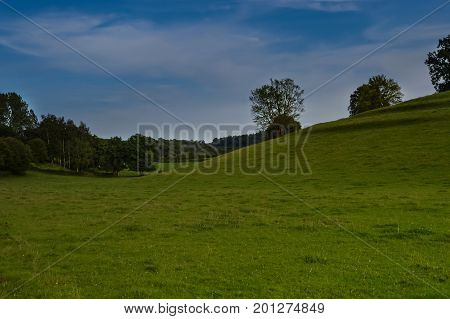 Landscape of meadow and trees in the Gaume on the side of the village of Gerouville