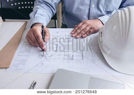 Engineering or Creative architect in construction project Engineers hands working on construction blueprint and building model at a workplace in office Building and architecture concept.