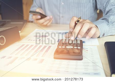 Business man or accountant working Financial investment on calculator with calculate Analyze business and market growth on financial document data graph and smart phone Accounting Economic commercial.