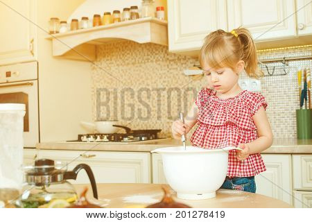 Cute Little Helper Girl Helping Her Mother Cooking In A Kitchen. Happy Loving Family Are Preparing B