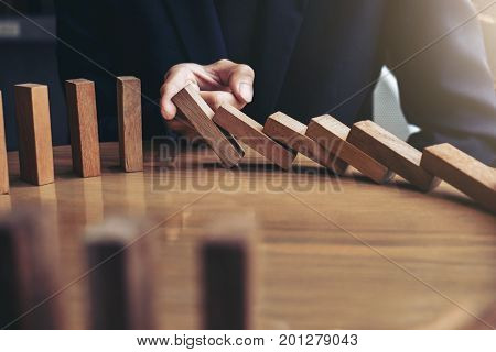 Close up of businessman hand Stopping Falling wooden Dominoes effect from continuous toppled or risk strategy and successful intervention concept for business.