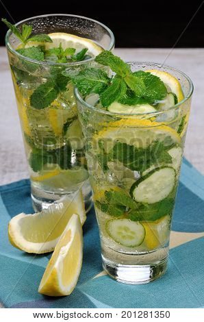 Refreshing cocktail cucumber mojito with lemon slices and mint