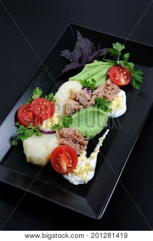Canned tuna with garnish of mashed potatoes with avocado.