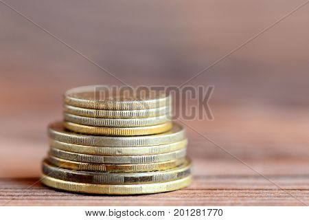 Tower of coins isolated on a wood background. Financial concept. Money. Closeup