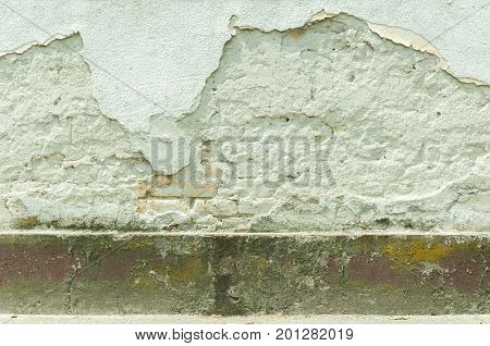 Bad house foundation with damaged bricks cracked plaster wall texture.