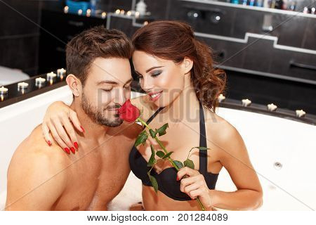 Young couple in jacuzzi man smelling red rose