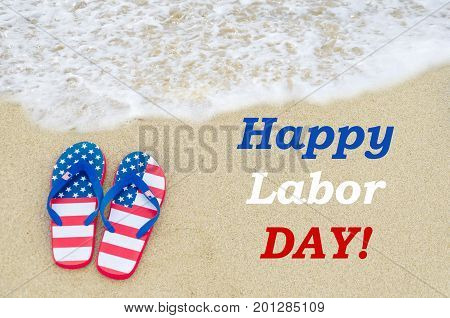 Labor day background on the sandy beach with flip flops of American flag colors
