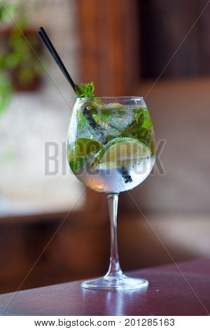 Glass tank mojito at the bar closeup. refreshing drink with Fresh mint, limes, sugar