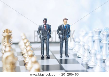 Two toy businessmen, lawyers or politicians on a chessboard. Business, politics or law concept.