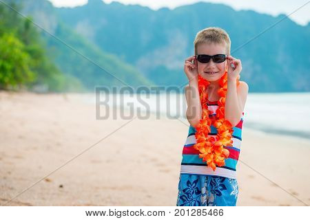 Boy Wearing Hawaiian Floral Lei On The Beach
