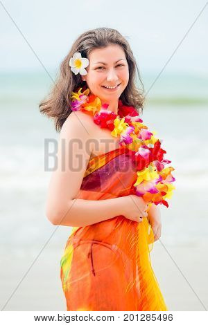 Vertical portrait of a happy woman in a pareo and flower lei