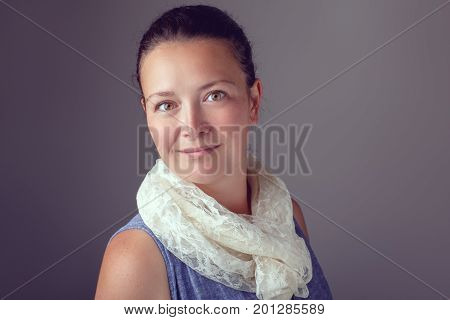 Portrait of smiling beautiful Caucasian brunette woman with dark hair and brown hazel eyes. Model in blue dress and white scarf posing in studio on plain light background. Natural beauty.