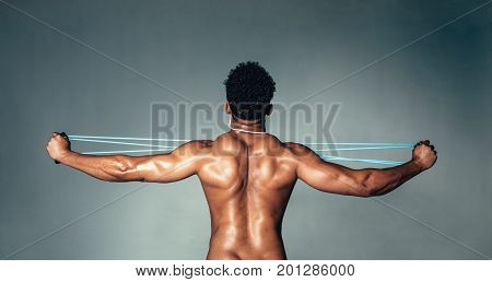 Rear view of muscular young man stretching arms with rubber band. Male bodybuilder doing exercises with elastic band on grey background.