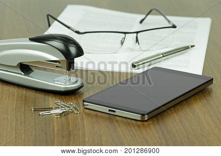 Still-life photography on office desk with stapler and office staples next to mobile phone in front of paper with glasses and pen - blurred background
