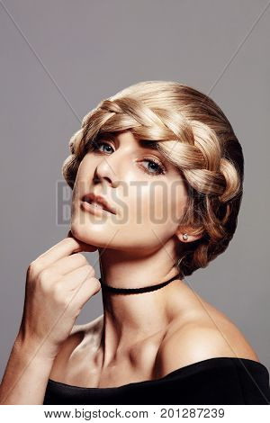 Portrait of young beautiful woman with blond hair and braid hairdo. Sensual female model with braid looking at camera against grey background.