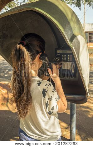 Girl Standing, Holding The Phone, On Her Back, Talking On The Public Phone