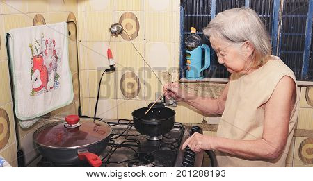 Old Woman With White Hair At Kitchen Using A Hashi