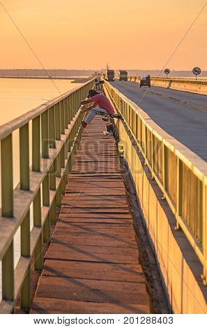 Sao Paulo Brazil - July 21 2017: Footpath for pedestrian crossing on Helio Serejo bridge with a man seated fishing from above the bridge. Tight path for pedestrians beside the highway on bridge.
