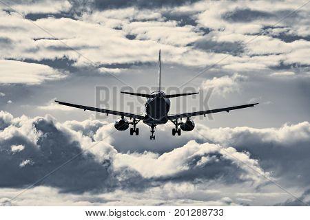 Landing of the passenger plane at sunset time.