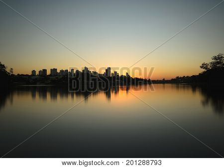 Londrina Brazil - July 24 2017: Sunset at Lago Igapo lake localized in Londrina city. The city silhouette and the water of the lake reflecting the sunset.