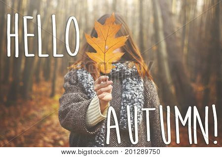 hello autumn fall text sign on stylish happy hipster girl in coat holding yellow leaf on the background of sunny autumn forest. seasonal greeting card concept. fall image