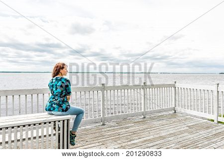 Young Woman Sitting On White Bench Overlooking Peaceful Saint Lawrence River In Quebec, Canada