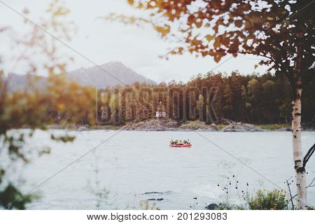 Tiny orthodox chapel or church in pine forest on the bank of Katun river in Russia Altai mountains captured on tilt-shift lens with people rafting on the center of river