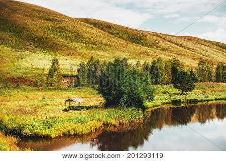 Autumn scenery with small lake of fresh water hills in distance green and yellow meadows of native grasses abandoned arbour with trees near Altai mountains Aya district Russia