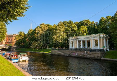 ST PETERSBURG RUSSIA - AUGUST 15 2017. Rossi Pavilion in the Michael Garden and the Moika river with floating pleasure boats in St Petersburg Russia. City landscape of St Petersburg Russia
