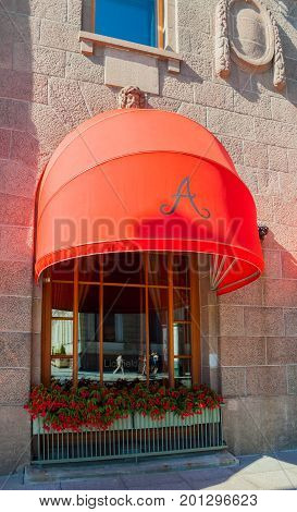 ST PETERSBURG RUSSIA - AUGUST 15 2017. Red awning of famous Astoria hotel at Bolshaya Morskaya street in St Petersburg Russia in sunny day -closeup facade street view of St Petersburg landmark