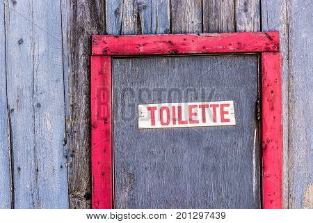 Red Painted Old Vintage Shed With Toilette Restroom Sign Closeup In Summer Countryside