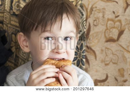 Hungry boy eating with appetite bakery bun with full cheeks