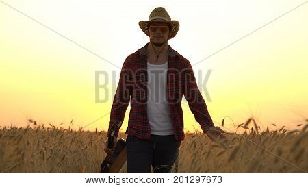 young guy walks the golden wheat field in the rays of the sunset and plays the guitar. Freedom concept