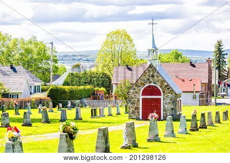 Ile D'Orleans Canada - June 1 2017: Red painted church chapel in cemetery and gravestones in summer