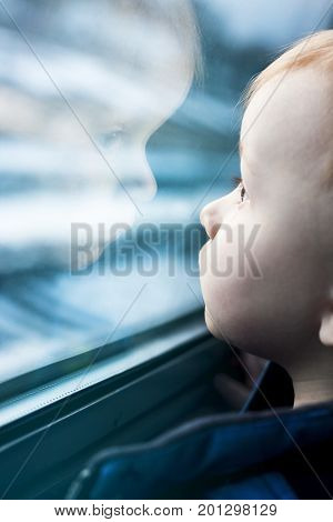 Toddler looking at reflection in window. Boy dreams about urban future. Technology influence on children