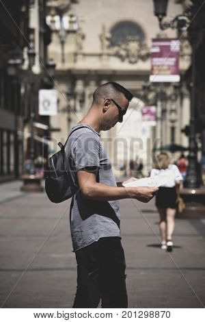 closeup of a young caucasian man on a pedestrian street of Zaragoza, Spain, observing a city map with the Cathedral-Basilica of Our Lady of the Pillar in the background