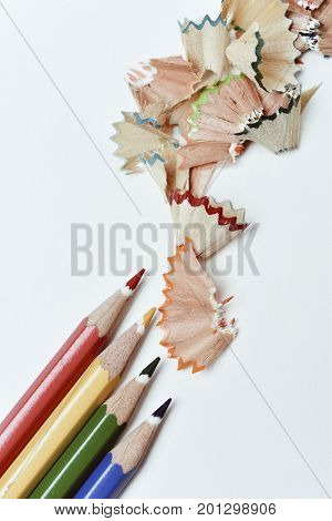 high-angle shot of a pile of pencil crayons of different colors and a pile of fan-shaped shavings of different colors on an off-white background