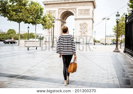 Lifestyle portrait of a young stylish business woman walking outdoors near the famous triumphal arch in Paris